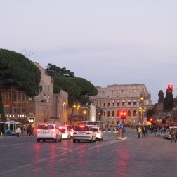 The via dei Fori Imperiali leading to the Colosseum is busy with traffic and tourists.